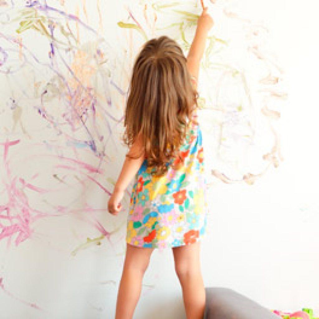 Niña pintando paredes